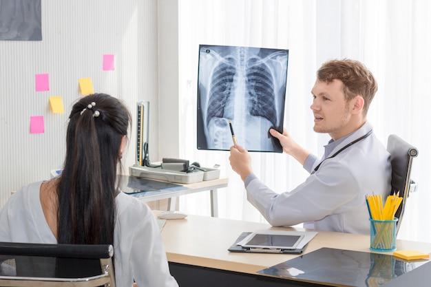 Homme médecin tenant une radiographie et conversation avec un patient asiatique jeune femme.