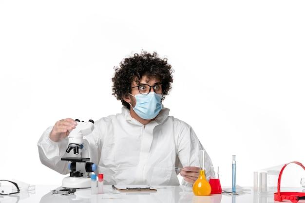 Homme médecin en tenue de protection et masque à l'aide d'un microscope sur blanc