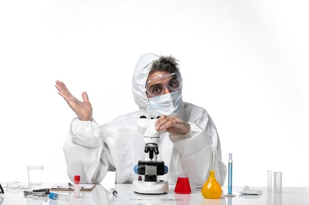 Homme médecin en tenue de protection et masque à l'aide de son microscope sur blanc