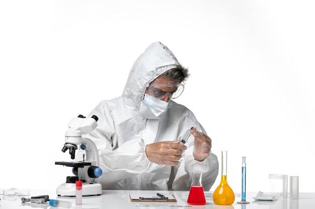 Homme médecin en tenue de protection avec masque stérile à l'aide d'injection sur blanc