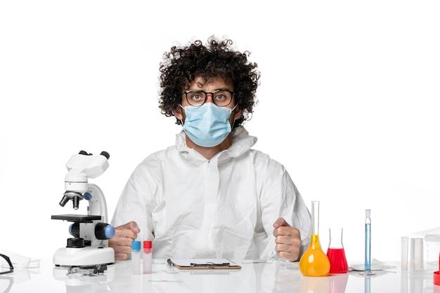Homme médecin en tenue de protection masque stérile assis sur blanc