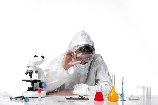 Homme médecin en tenue de protection avec masque stérile sur blanc
