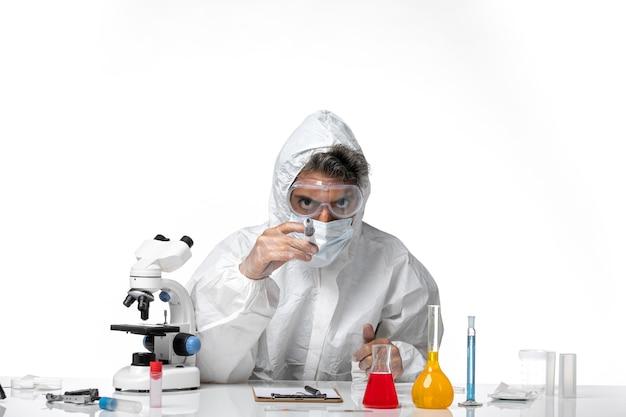 Homme médecin en tenue de protection avec masque stérile tenant l'injection sur blanc