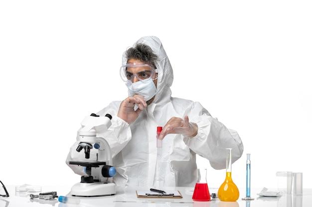 Homme médecin en tenue de protection et avec masque tenant une fiole sur blanc