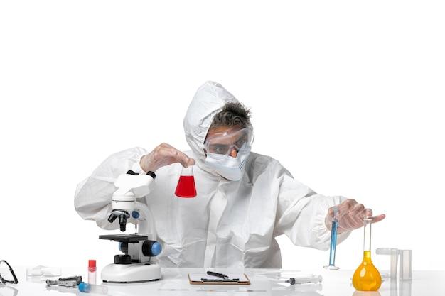 Homme médecin en tenue de protection et avec masque tenant une fiole avec une solution rouge sur blanc clair
