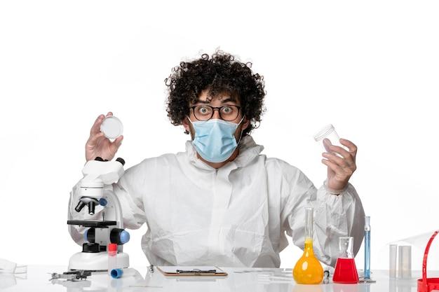 Homme médecin en tenue de protection et masque tenant des flacons sur blanc