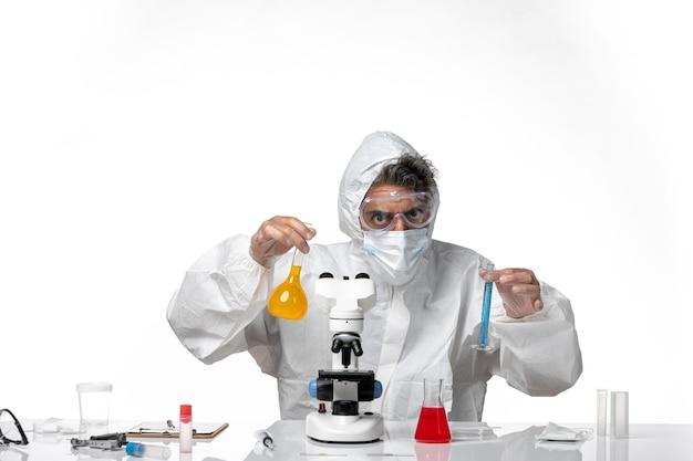 Homme médecin en tenue de protection et masque tenant des flacons avec des solutions sur blanc