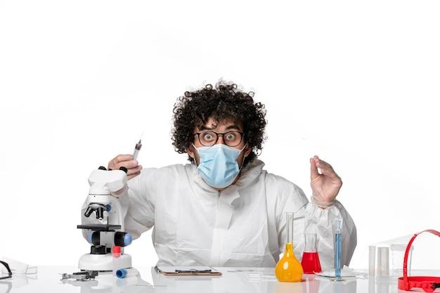 Homme médecin en tenue de protection et masque travaillant avec des injections sur blanc