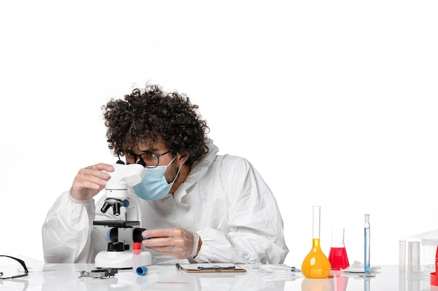 Homme médecin en tenue de protection et masque travaillant avec microscope sur blanc