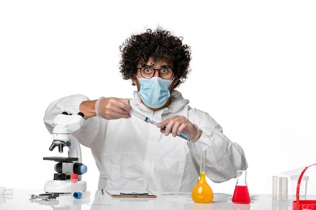 Homme médecin en tenue de protection et masque travaillant avec une solution sur blanc