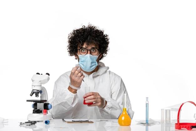 Homme médecin en tenue de protection et masque travaillant avec des solutions sur blanc clair