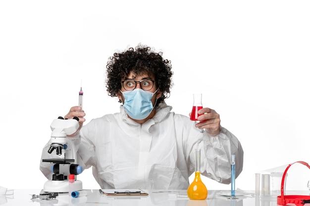 Homme médecin en tenue de protection et masque travaillant avec des solutions sur blanc
