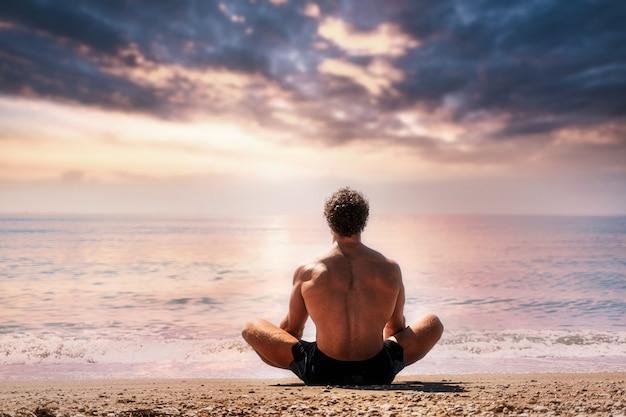 L'homme médite sur la vue sur la plage de sable de l'arrière