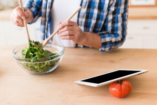 Homme, mélange, légume feuilles, à, cuillère bois, dans, les, bol verre, à, tablette numérique, et, tomate, sur, bureau bois