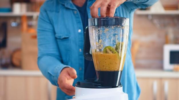 Homme mélangeant des fruits avec un mélangeur pour un délicieux smoothie dans la cuisine. joyeuse famille faisant ensemble du jus de fruits frais et nutritif biologique sain pour le petit-déjeuner à partir de fruits frais tout en suivant un régime.