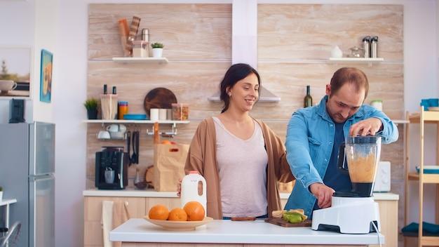 Homme mélangeant des fruits pour un smoothie à l'aide d'un mélangeur dans la cuisine. joyeux jeune couple. joyeuse famille faisant ensemble du jus de fruits frais et nutritif bio sain pour le petit-déjeuner à partir de fruits frais pendant un séjour