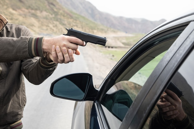 L'homme menace le conducteur avec une arme à feu