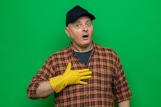 Homme de ménage en chemise à carreaux et casquette portant des gants en caoutchouc à la surprise de tenir la main sur sa poitrine