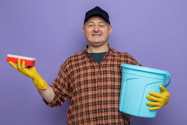 Homme de ménage en chemise à carreaux et casquette portant des gants en caoutchouc tenant une éponge et un seau regardant la caméra heureux et positif souriant joyeusement debout sur fond violet