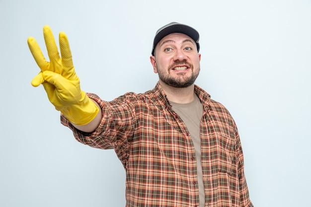 Homme de ménage slave souriant avec des gants en caoutchouc faisant trois gestes avec les doigts
