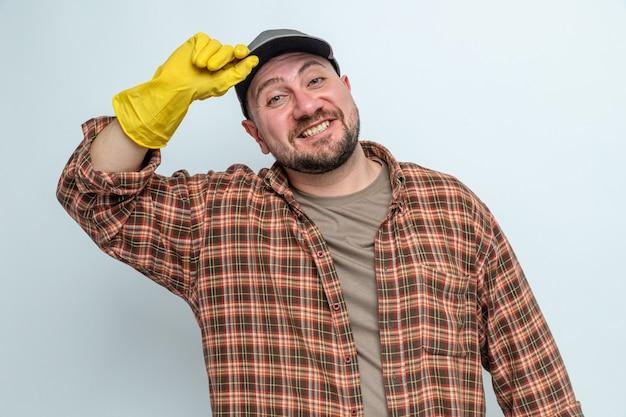Homme de ménage slave souriant avec des gants en caoutchouc regardant à l'avant