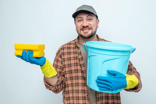 Homme de ménage slave souriant avec des gants en caoutchouc tenant un seau et une éponge