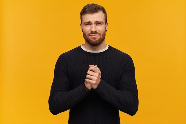 Homme mendiant barbu aux cheveux bruns. ça a l'air regrettable. a un piercing. porter un pull noir. tient les paumes ensemble. plaidez pour quelque chose. isolé sur mur jaune