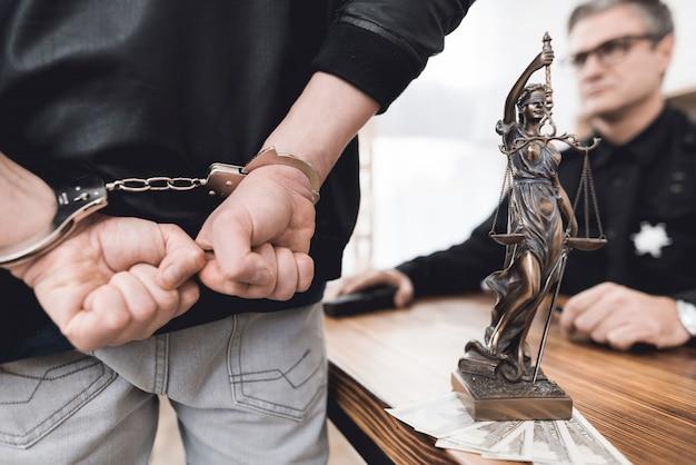 Un homme menottes aux poignets se tient devant un policier.
