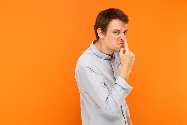 Homme menteur touchant le nez et regardant la caméra