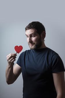 Homme en merde noire tenant un coeur rouge dans une pince à épiler avec un visage sérieux pensant à la question, idée très confuse