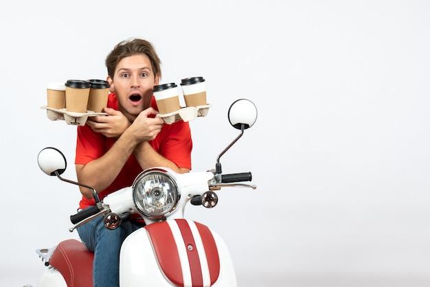 Homme de messagerie surpris en uniforme rouge assis sur la moto de livrer des commandes sur fond blanc