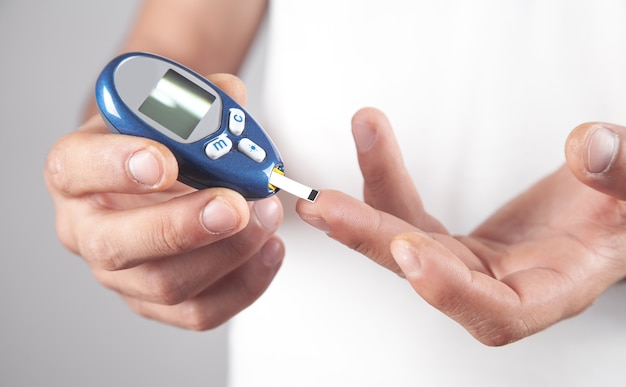 Homme mesurant le niveau de glucose à la maison.