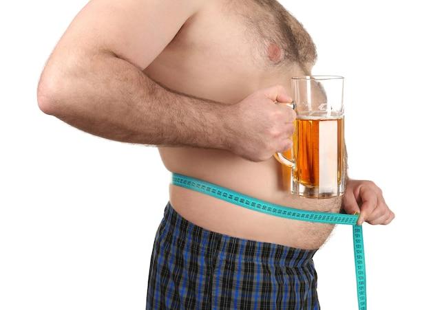 Homme mesurant le ventre et tenant un verre de bière sur fond blanc