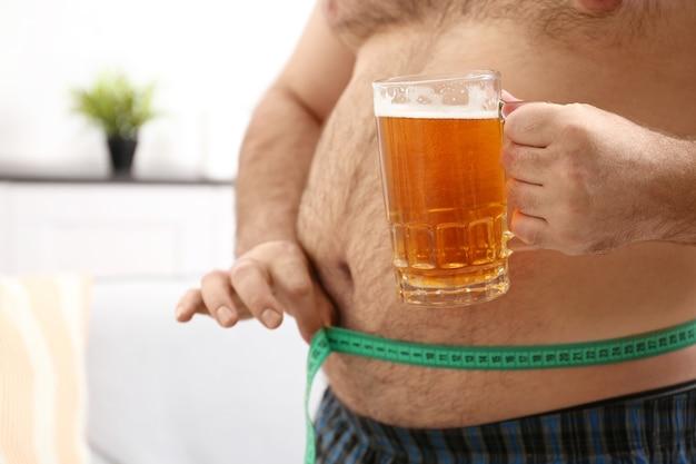 Homme mesurant le ventre et tenant un verre de bière à la maison