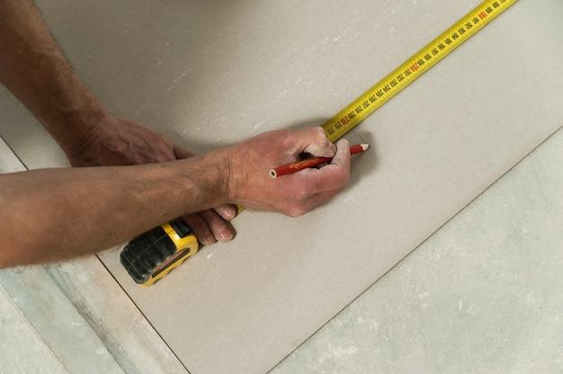 L'homme mesure la cloison sèche