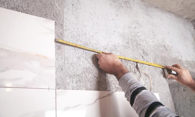 L'homme mesure le mur. mesures et coupe de carreaux