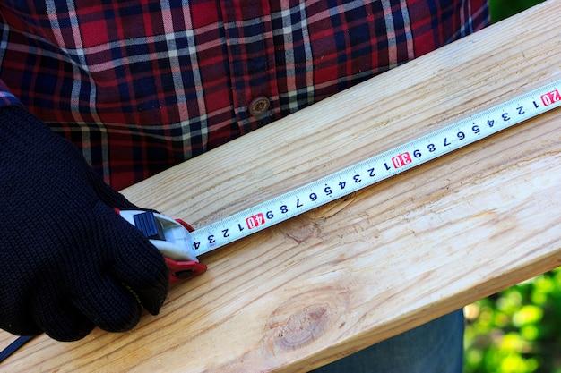 L'homme mesure la planche avec un atelier de menuiserie à ruban à mesurer dans l'arrière-cour