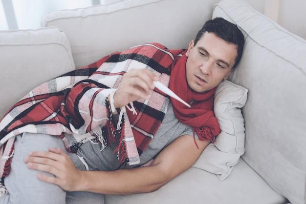 Un homme mesure sa température avec un thermomètre électronique.