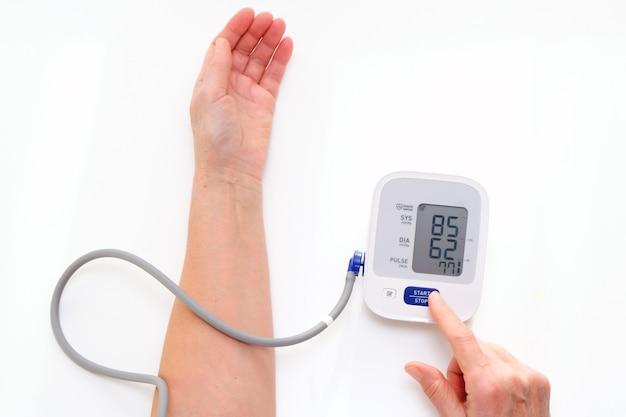 L'homme mesure la tension artérielle, fond blanc. hypotension artérielle. main et tonomètre se bouchent.