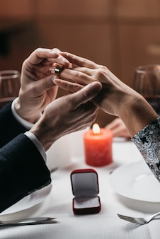 L'homme met l'anneau à la main de sa femme.