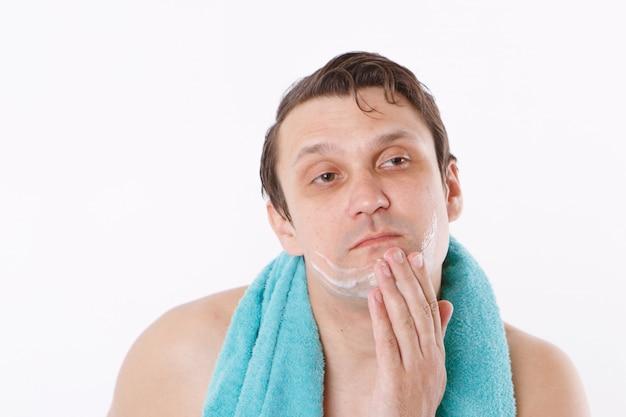 Un homme met un après-rasage sur son visage. le gars lui caresse le visage. soins du matin dans la salle de bain. copie espace