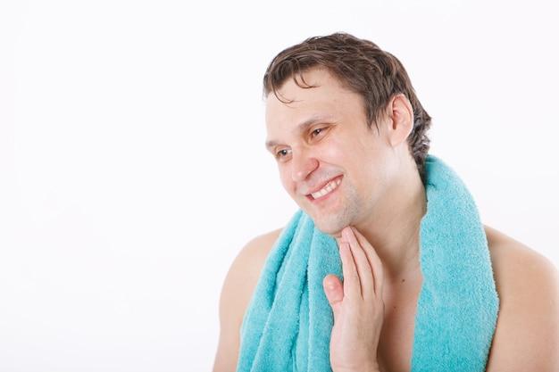 Un homme met un après-rasage sur son visage. le mec lui caresse le visage. soins du matin dans la salle de bain. copie espace
