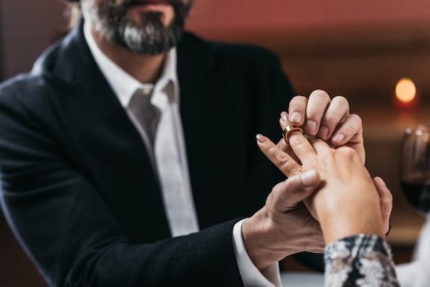 L'homme met la bague à portée de main pour sa femme close-up. focus sur la bague