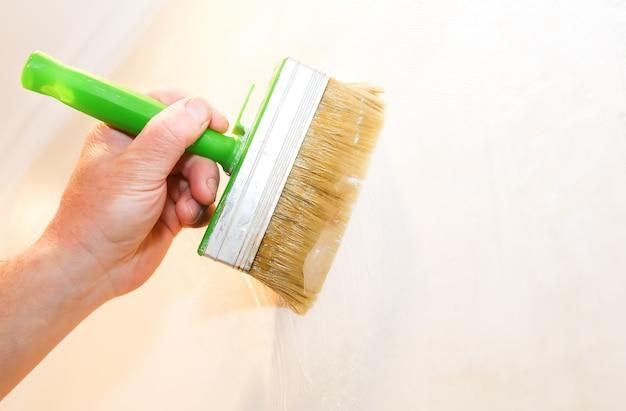 L'homme met de la colle sur le mur avec une brosse. pose de papier peint. travaux de réparation d'entretien rénovation dans l'appartement. restauration à l'intérieur.