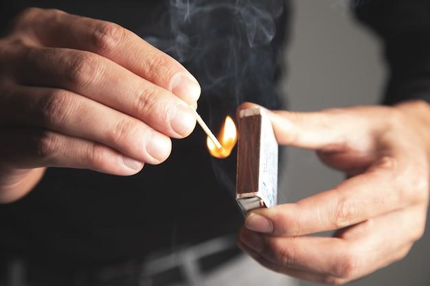 Un homme met le feu à une allumette en bois