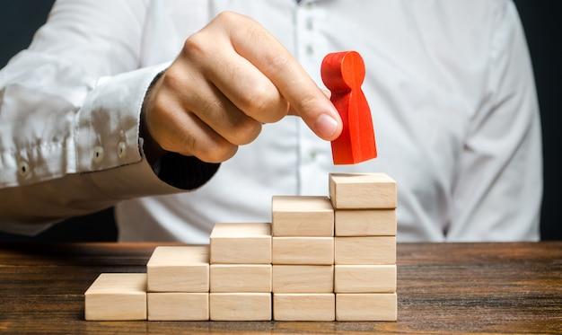 Un homme met une figure humaine rouge en haut des escaliers amélioration des compétences de croissance de carrière