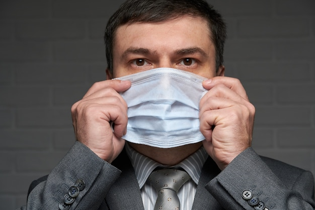 Un homme met un masque sur son visage pour une protection individuelle antivirus - concept de soins de santé et de médecine, conseils de prévention