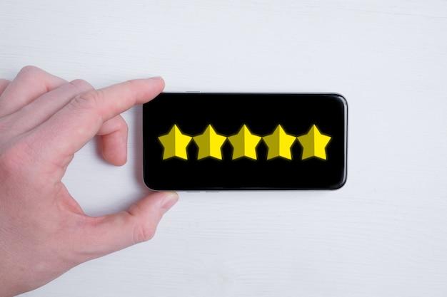 Un homme met une note abstraite de cinq étoiles dans un smartphone sur un blanc. meilleur score. mise à plat.