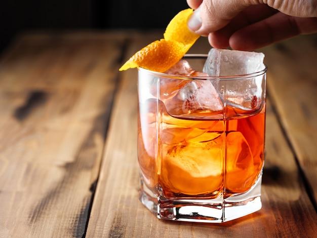 Un homme met une peau d'orange sur un rocher. cocktail negnoni. espace de copie.