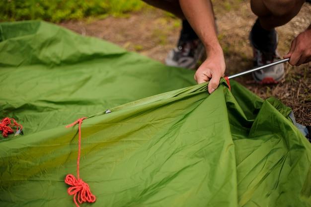 Homme met en place une tente verte mettant dans un cadre en métal